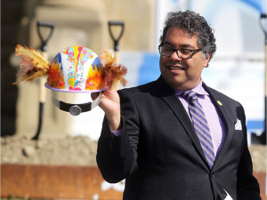 Mayor Naheed Nenshi takes a closer look at the artistic hard hat he used during the ground breaking of cSPACE King Edward in Marda Loop on May 13, 2015. (Colleen De Neve/Calgary Herald)