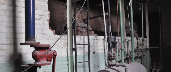 Brick removed to reveal historic boiler heat return drums