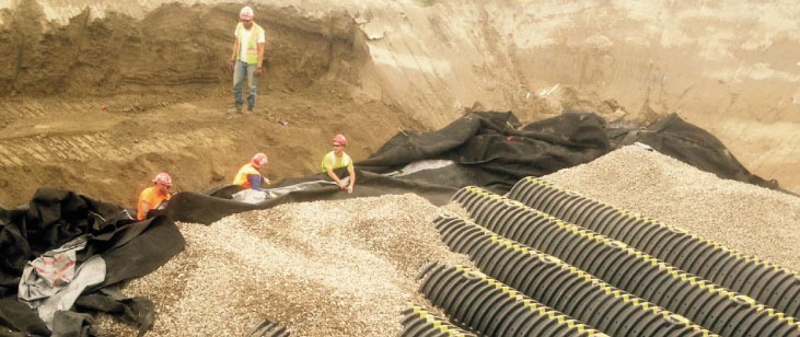 Crew  holds membrane with remaining backfill covering cisterns from view