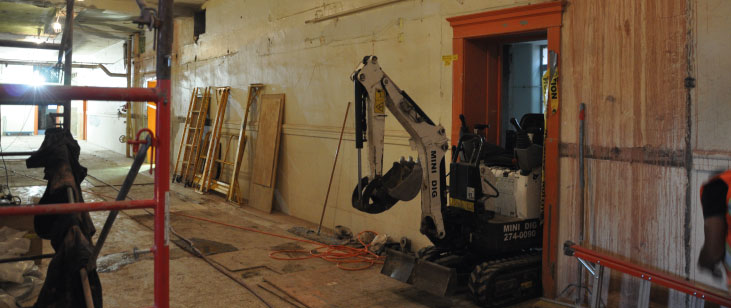 Small excavator fits through doorway of former boys washroom