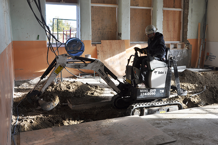 Excavator making trench in future Montessori classroom space
