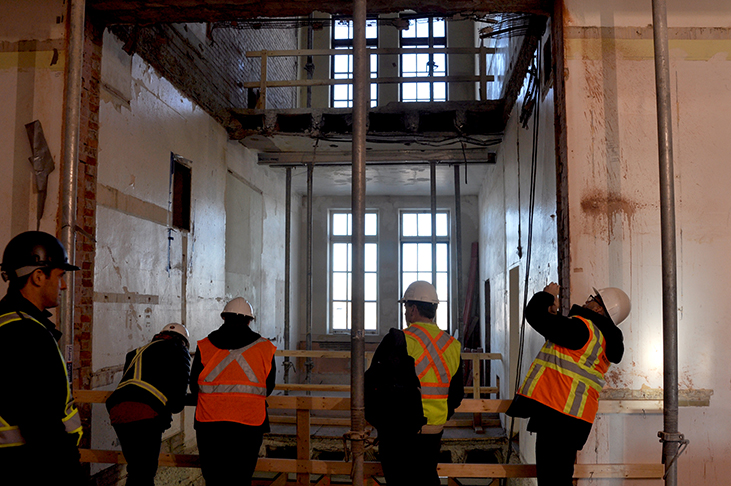 Architect team admires the newly instated elevator shaft opening