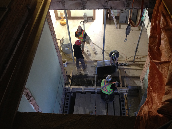 Sam and Scott pour ring beam before 4th floor bricklaying can resume