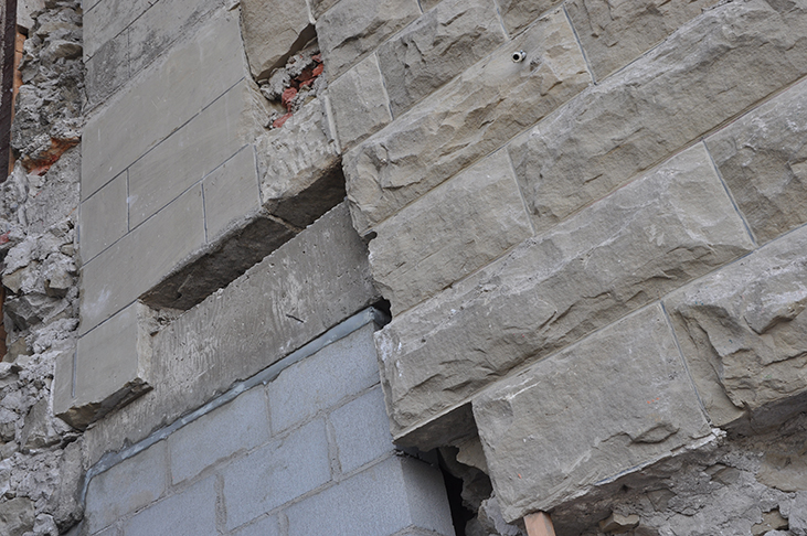 Pattern of historic sandstone block both rough and smooth along with cinder block repair
