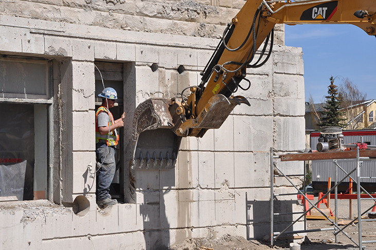 Excavator set to carefully remove several thousand pounds of concrete wall section