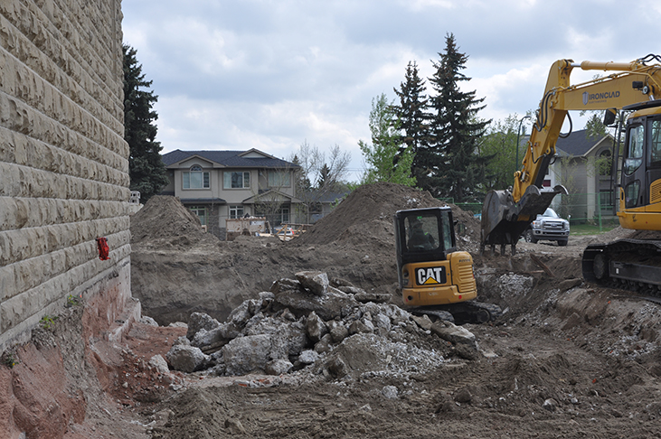 Excavators remove concrete foundation debris