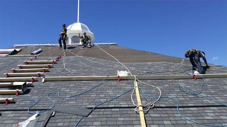Roofers at work on steep sloped roof