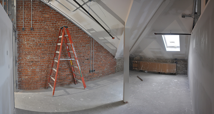 Exposed brick and skylight in attic studio